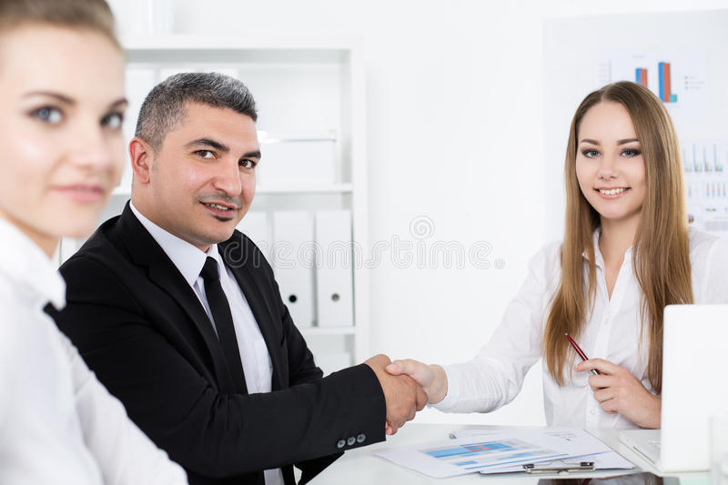 Businessman in suit shaking business woman's hand. Businessman in suit shaking young business woman's hand. Partners made deal and sealed it with handclasp stock image