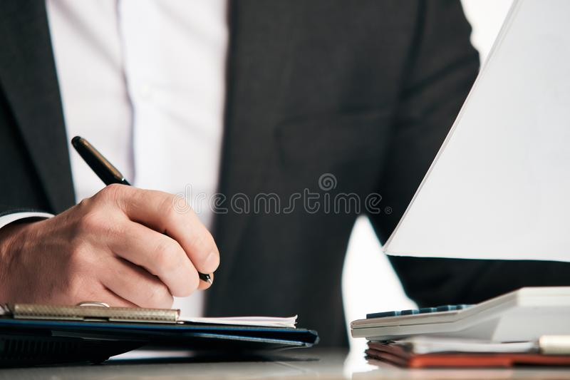 Businessman in a suit signing or writing a document agreement royalty free stock images