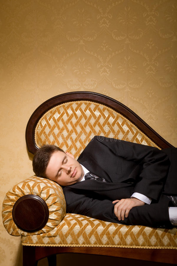 Businessman in suit sleeping on sofa in room. Businessman in suit sleeping on sofa in luxury room royalty free stock photography