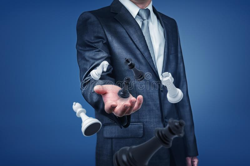 A businessman in suit standing with only upper-body visible, holding his hand out as if to reach chesspieces floating in stock photography