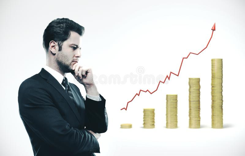 Businessman in suit thinking. And  looking on gold coins chart. Business success concept stock photography