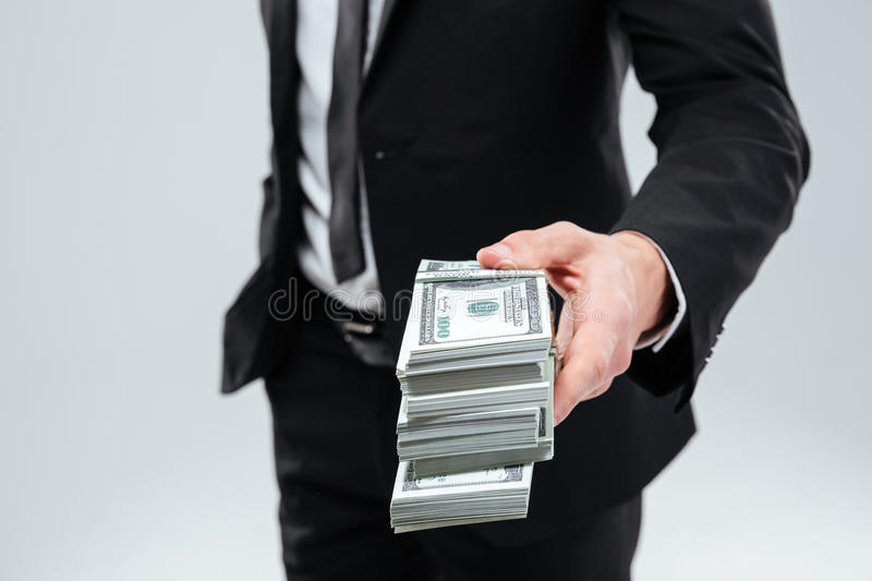 Businessman in suit and tie giving money to you stock photo