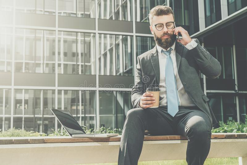 Businessman in suit and tie is sitting outside on bench,drinking coffee and talking on his cell phone.Nearby is laptop. stock photography