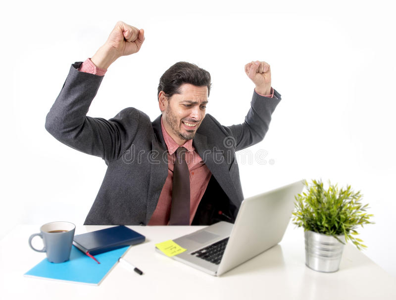 Businessman in suit and tie working at office computer desk doing victory sign with his arms happy and excited. Young attractive Latin businessman in suit and royalty free stock photos
