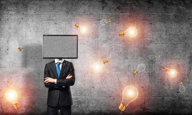 Businessman with TV instead of head. Businessman in suit with TV instead of head keeping arms crossed while standing among flying lightbulbs and with gray dark stock photography