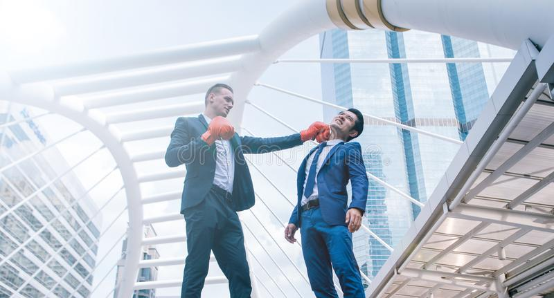 Businessman in suit uniform wearing boxing gloves and punching business man`s face royalty free stock image
