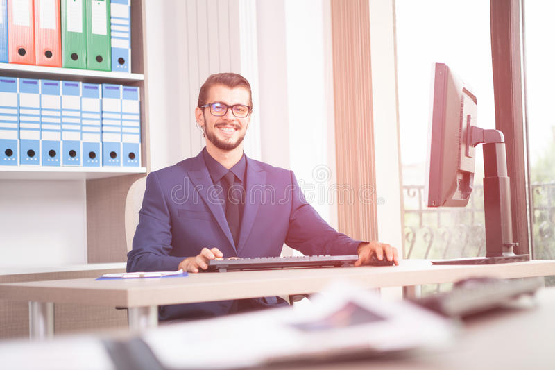Businessman in suit working at his computer next to a glass wind royalty free stock image