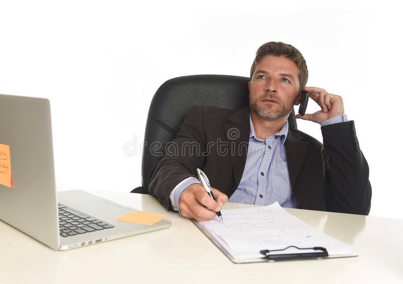 Businessman in suit working at laptop computer desk talking on mobile phone at modern office. Young attractive businessman in suit working at laptop computer stock photo