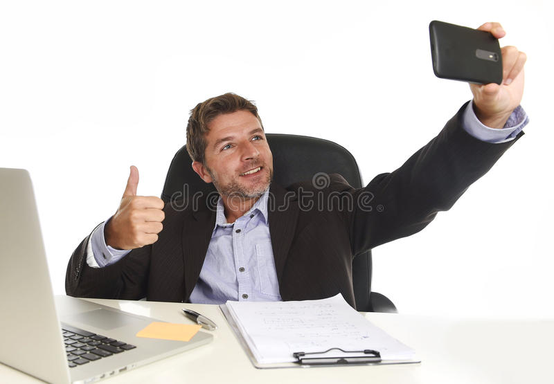 Businessman in suit working at office laptop computer desk using mobile phone for taking selfie photo. Young attractive and happy businessman in suit working at royalty free stock photos