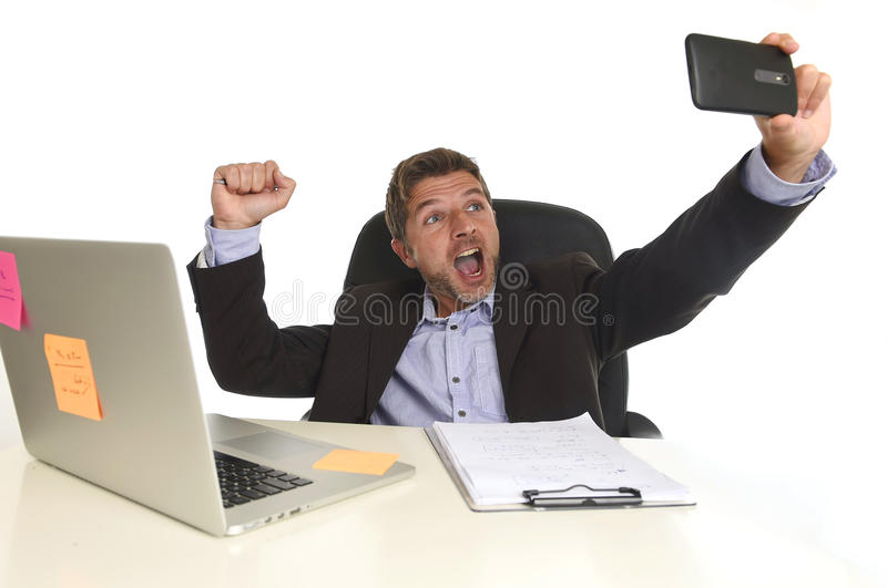 Businessman in suit working at office laptop computer desk using mobile phone for taking selfie photo. Young attractive and happy businessman in suit working at stock image