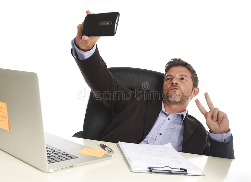 Businessman in suit working at office laptop computer desk using mobile phone for taking selfie photo. Young attractive and happy businessman in suit working at royalty free stock images