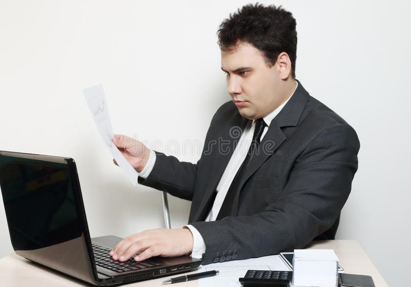 Businessman in suit works with laptop and documents stock images