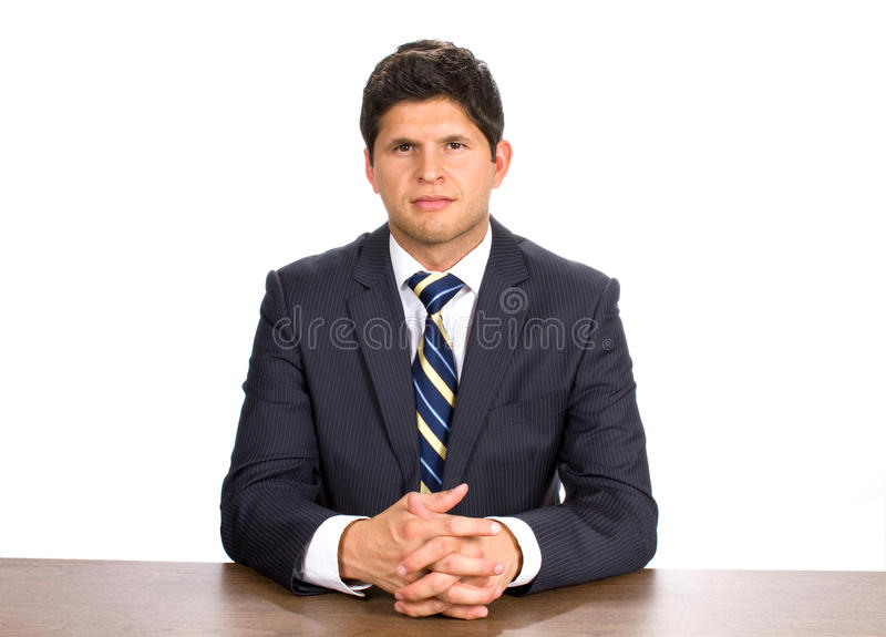 Businessman In Suit. Young businessman wearing a pin stripe suit sits at a table with his hands interlaces stock photography