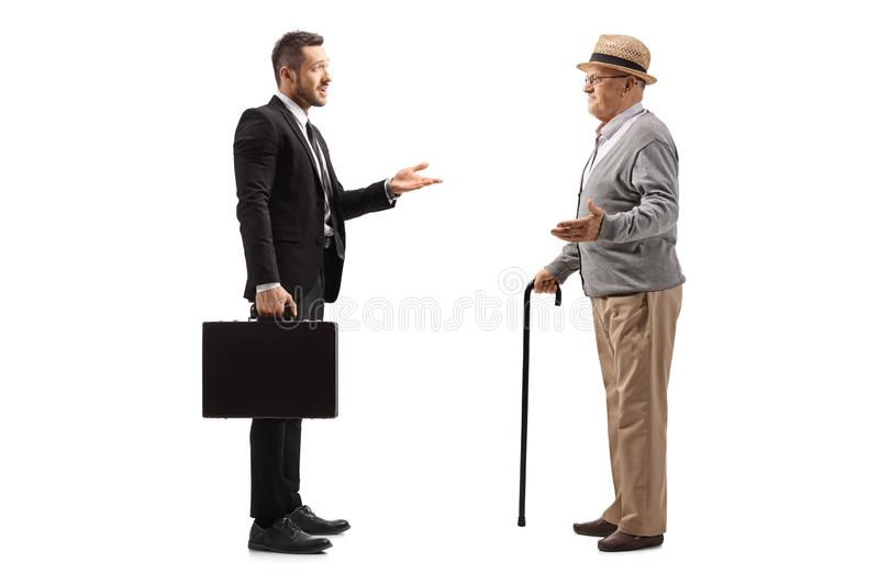 Businessman with a suitcase having a conversation with an elderly gentleman stock photography
