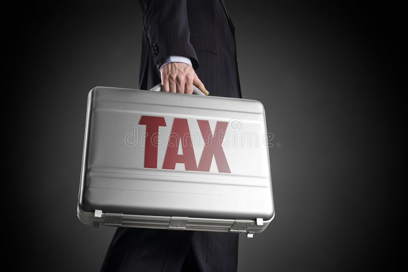 Businessman with suitcase with letters TAX on a dark background royalty free stock image