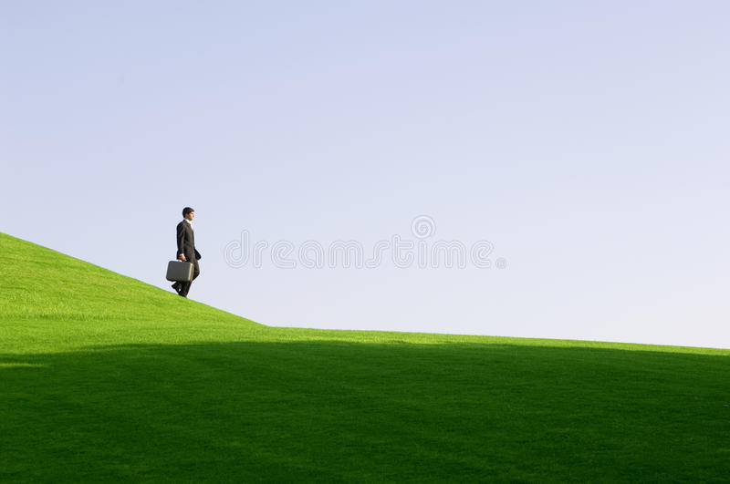 A businessman with a suitcase walking down hill stock image