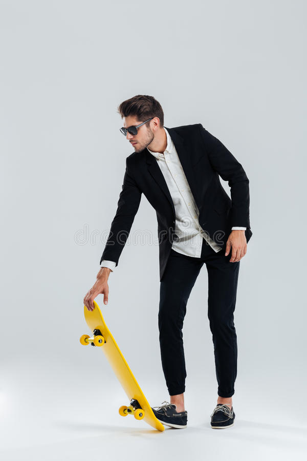 Businessman in sunglasses and suit going to ride a skateboard royalty free stock photography