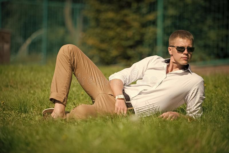 Businessman in sunglasses on sunny outdoor. Man relax on green grass. Handsome macho enjoy summer day. Fashion style and stock image