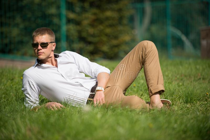 Businessman in sunglasses on sunny outdoor. Man relax on green grass. Handsome macho enjoy summer day. Fashion style and royalty free stock photography