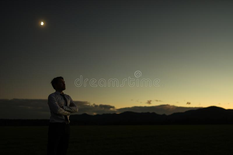 Businessman at sunset standing outdoors with folded arms stock photos