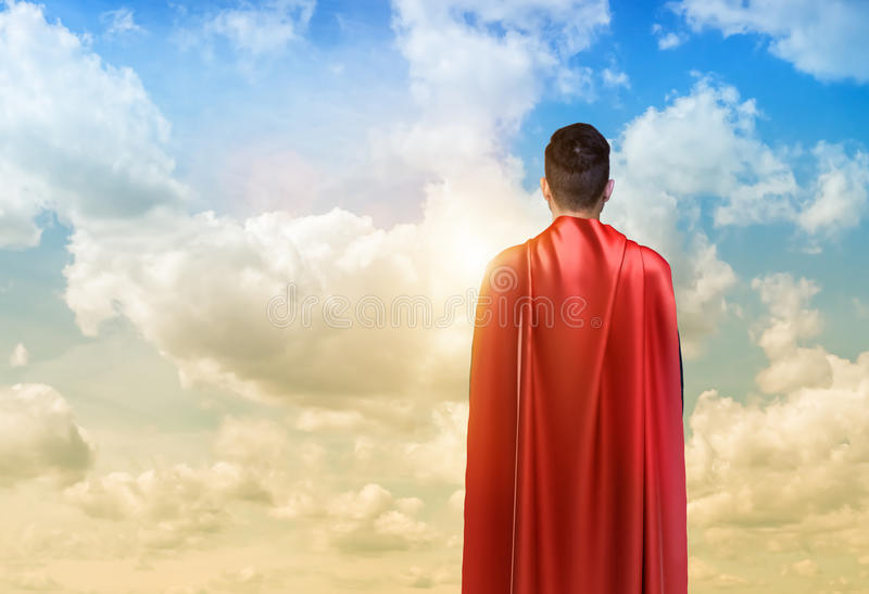 A businessman in super hero cape standing turned back on the sky background. Business hero. Confidence and success. New opportunities royalty free stock photo