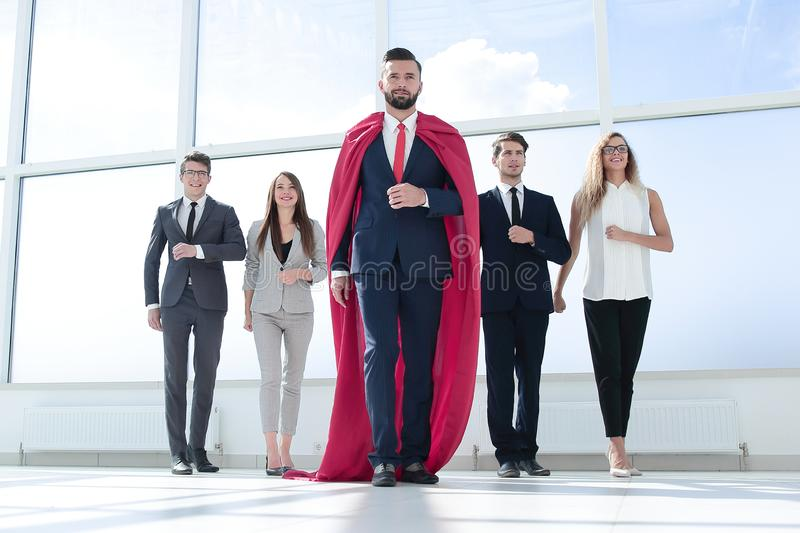Businessman-superhero and business team standing in the office. royalty free stock photo