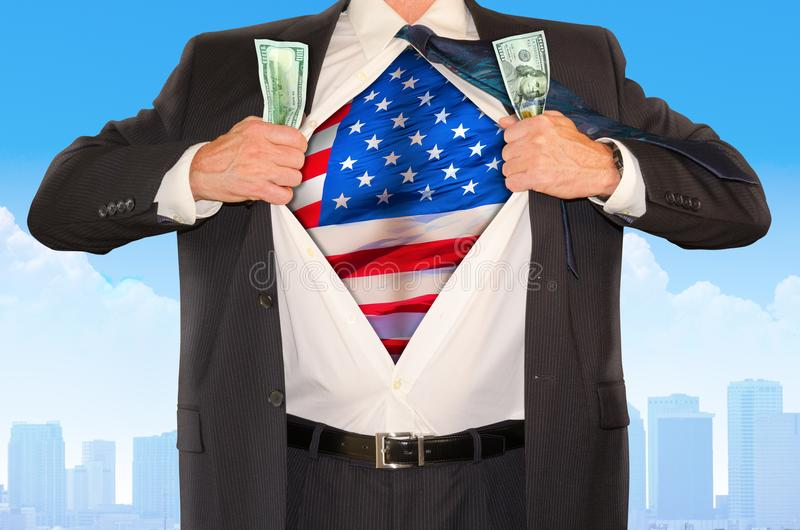 Businessman superhero clutching money and opening shirt to reveal United States of America flag stock images