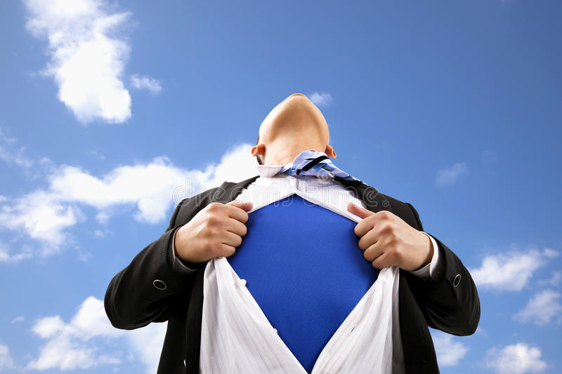 Businessman and superman concept. Businessman pulling his t-shirt open stock photography