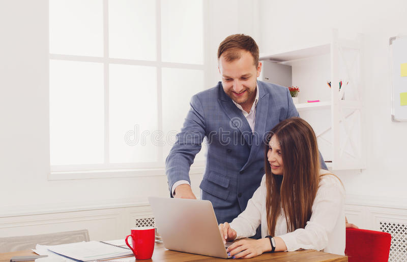 Businessman supervising his female assistant's work on laptop computer royalty free stock photo