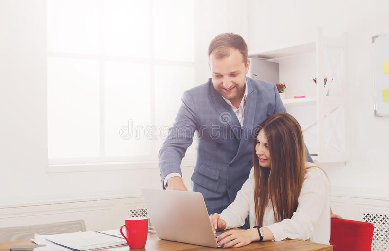 Businessman supervising his female assistant's work on laptop computer royalty free stock photos