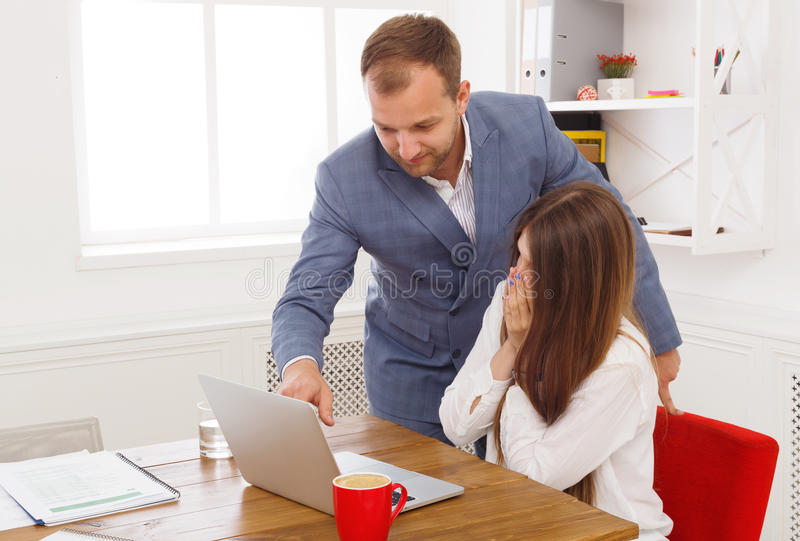 Businessman supervising his female assistant`s work on laptop stock photos