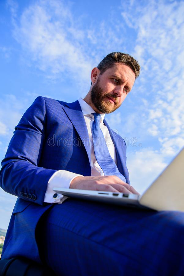 Businessman surfing internet or reply emails while sit with laptop outdoors. Increase online sales tips. Tips create stock photography