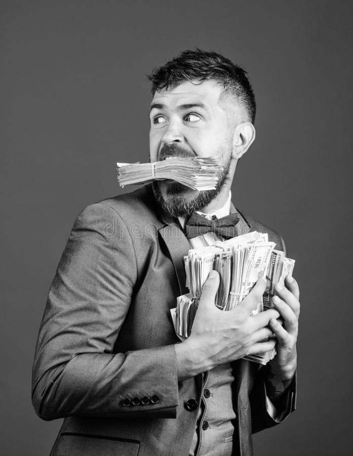 Businessman surprised feels like thief with lot of cash in hands. Steal money. Thief with piles dollars money. Earnings. Surprise concept. Man bearded royalty free stock image