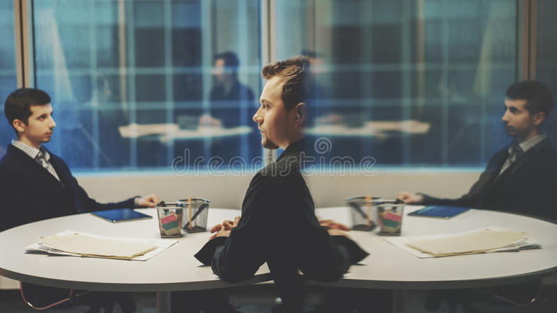 Businessman surrounded by reflections. Young serious successful men entrepreneur in black shirt with a beard, trying to take a favorable decision during meeting stock photography