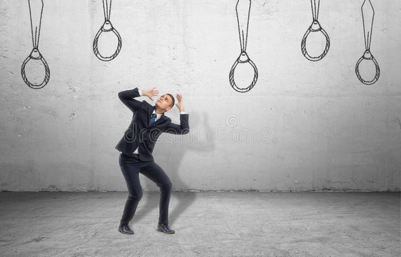 Businessman surrounded by ties drawn on wall, which look like nooses. stock image