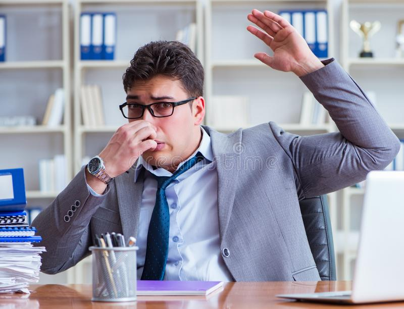 Businessman sweating excessively smelling bad in office at workp royalty free stock images