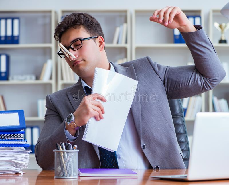 Businessman sweating excessively smelling bad in office at workp royalty free stock photos