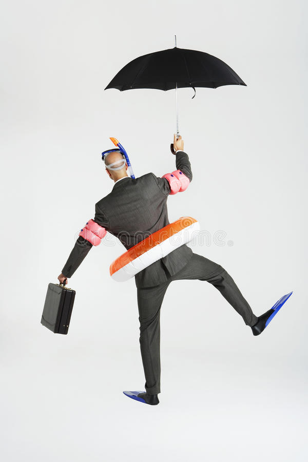 Businessman In Swimming Gear With Briefcase And Umbrella. Rear view of a businessman in swimming gear holding briefcase and umbrella against white background royalty free stock photos