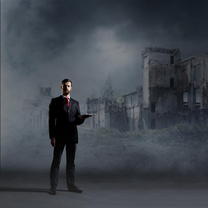 Businessman standing over apocalyptic background. Crisis, default, setback concept. stock image