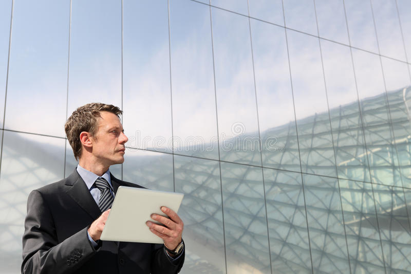 Businessman with tablet that looks far into the sky. In a scene of urban building with many glass windows stock photography