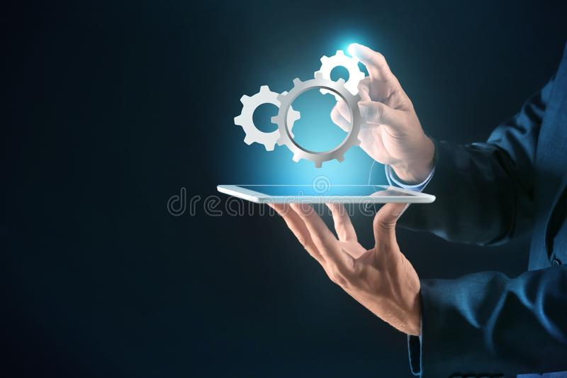 Businessman with tablet PC and digital gearwheels on dark background. Concept of Internet and technical support service royalty free stock image