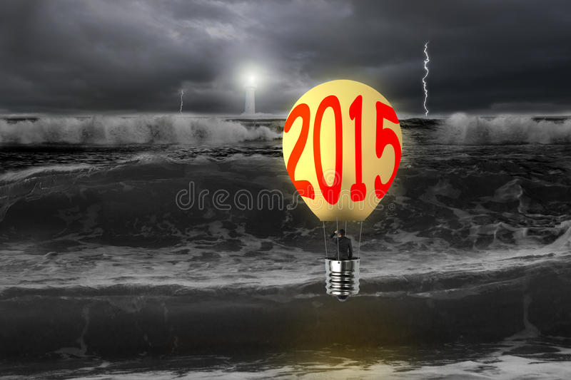 Businessman take 2015 bulb-shaped hot air balloon with dark ocean. Businessman take 2015 bulb-shaped hot air balloon with lighthouse in lightning dark ocean royalty free stock photos