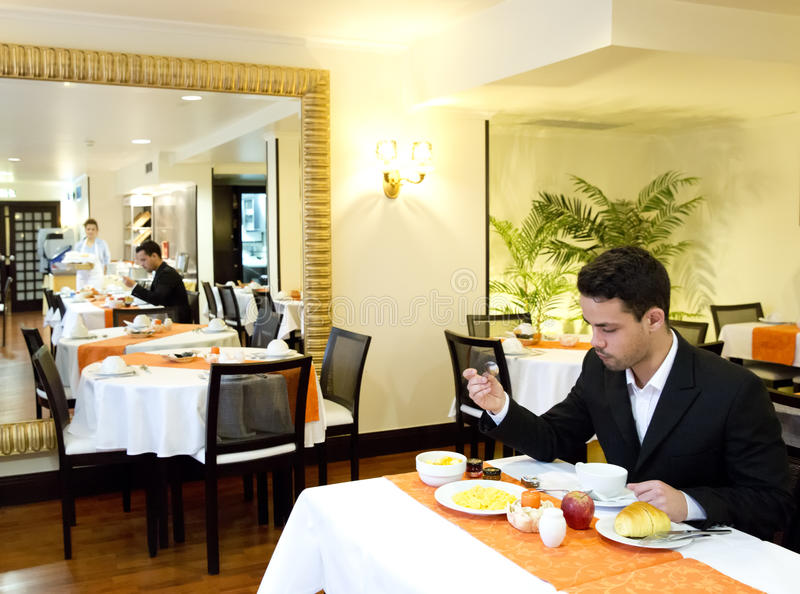 Businessman takes breakfast in hotel royalty free stock photography