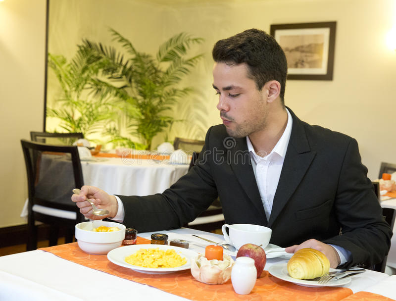 Businessman takes breakfast in hotel stock images
