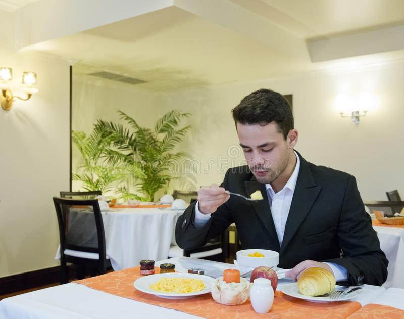 Businessman takes breakfast in hotel stock photography