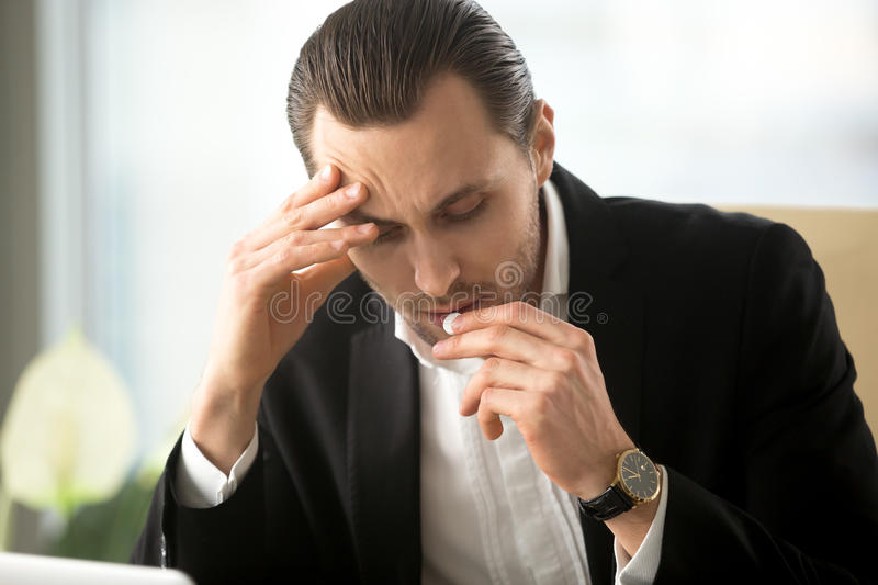 Businessman takes pill from headache in office royalty free stock photos