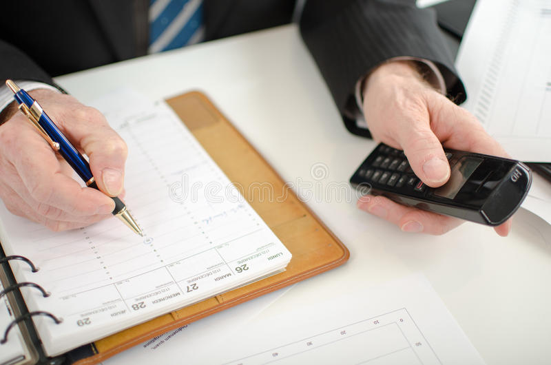 Businessman taking an appointment in his diary royalty free stock images