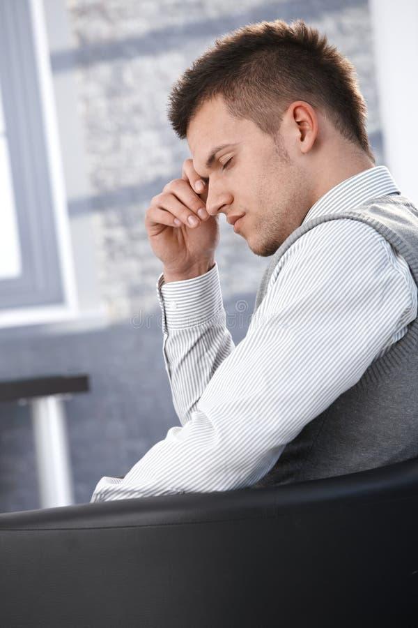 Businessman taking a break in armchair stock image
