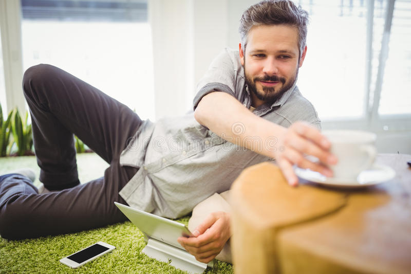 Businessman taking coffee cup while relaxing at creative office stock photo