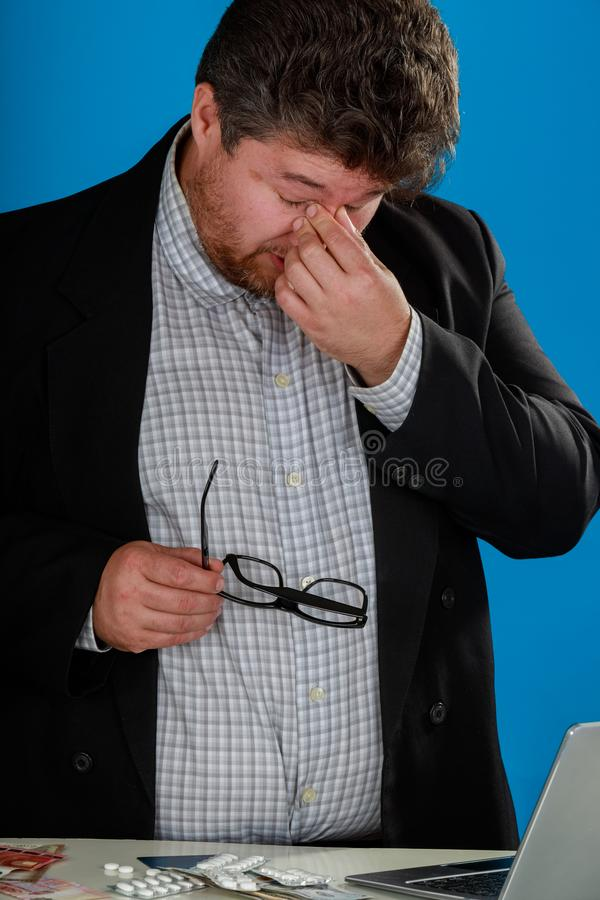 Businessman taking off glasses feels eye strain tension tired of with laptop, millennial guy has bad sight vision problem massagin stock image